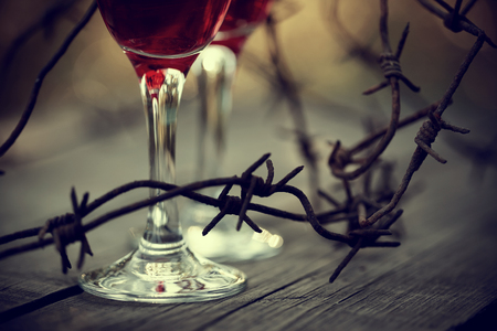 Rusty barbed wire and glasses with red wine on a table.  Alcoholic dependence. Stock Photo