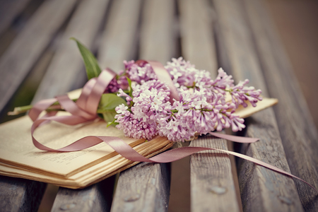 Lilac branch with a tape on the old book on a bench.