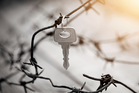 The key hangs on a rusty barbed wire. Stock Photo