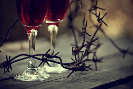 alcoholic drink: Glasses with alcoholic drink and a rusty barbed wire on a wooden table. Alcoholic dependence. Stock Photo