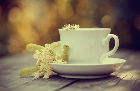 Tea with flowers of a linden in a white cup on a wooden table.