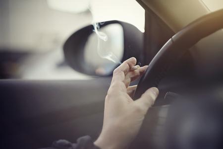 Smoking cigarettes at the wheel while driving a car.