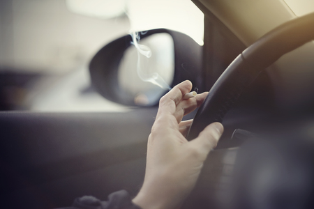 Smoking cigarettes at the wheel while driving a car. Imagens - 79140276