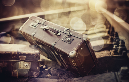 Two old vintage suitcases lie on railway rails. Stock Photo