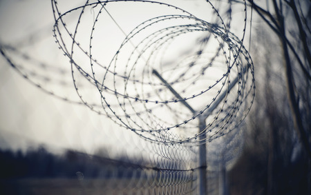 Abstract blurred background with coils of barbed wire. Banco de Imagens