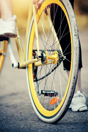 The rear wheel of the yellow sports bike. Sports bike ride in the Park. Outdoor activity. 免版税图像
