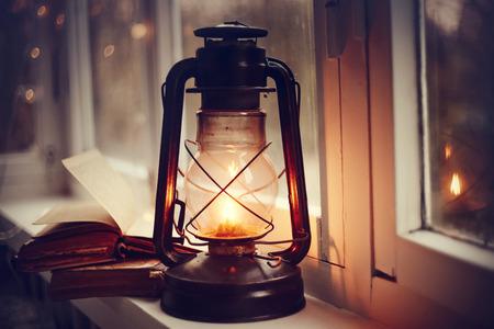 Lámpara de queroseno y libros viejos en el alféizar de la ventana. Foto de archivo