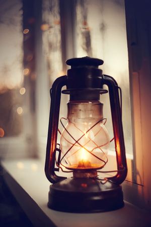 Vintage kerosene lamp stands on a white windowsill in the evening
