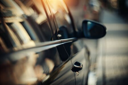 Reflection of the building in the shiny surface of the car. The window and door of the car. Background with the side surface of the car.