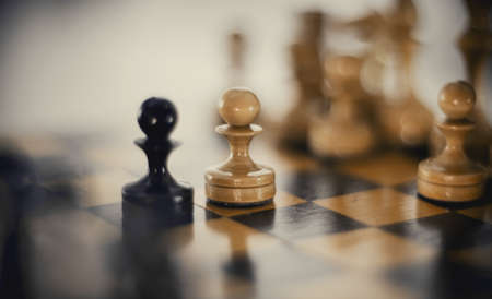 Two chess pieces are pawns: black and white. Wooden chess pieces on the chessboard. Intellectual game -chess. Chess pieces on the Board. A game of chess. Standard-Bild