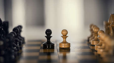 Two pieces on the chessboard are pawns: black and white. Wooden chess pieces on the chessboard. Intellectual game -chess. Chess pieces on the Board. A game of chess.