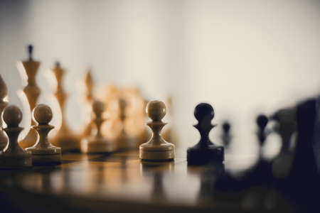 Two chess pieces are pawns: black and white. Wooden chess pieces on the chessboard. Intellectual game -chess. Chess pieces on the Board. A game of chess. Silhouettes of chess pieces. Standard-Bild