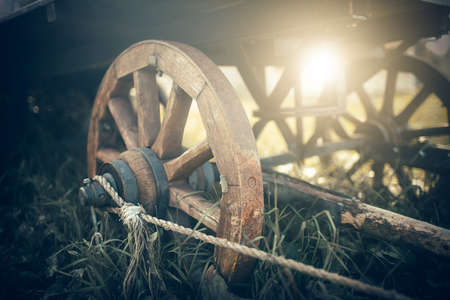 The wooden wheels of a cart standing in the grass. An old horse-drawn carriage. An old abandoned unnecessary cart. Banque d'images