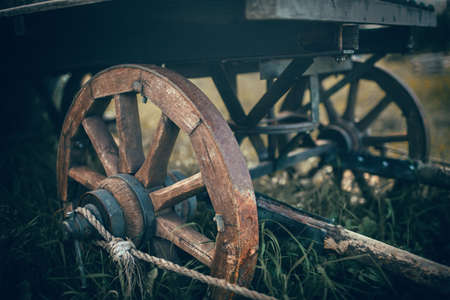 The wooden wheel of a cart standing in the grass. An old horse-drawn carriage. An old abandoned unnecessary cart.