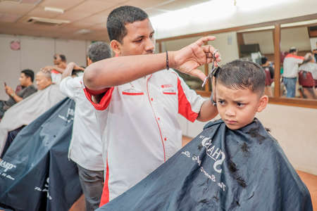 Muadzam Shah, Malaysia - August 14th, 2017 : Little boy getting warber while sitting haircut on chair at barbershop. Editorial