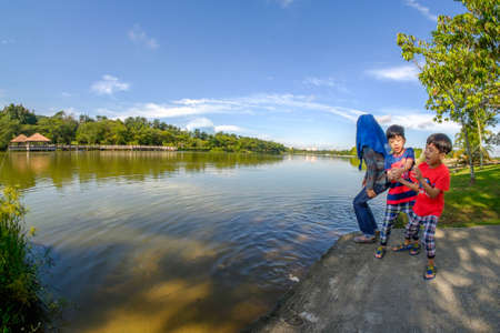 Putrajaya, Malaysia – September 24th, 2017 : Young girl with her young brotherS feeding carps in tropical pond at Wetland Putrajaya. Editorial