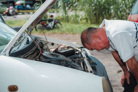 Segamat, Malaysia - November 11th , 2017 : Automobile air-conditioner servicing. Mechanic checking cooling system in car engine. Editorial