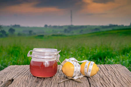 Fresh organic honey in glass jar , measuring tape , lemon and alarm clock on old wooden with blurred background ,healthy nutrition,strengthening immunity, diet and treatment of flu