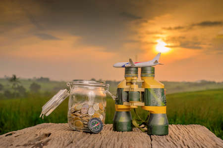 Saving planning for Travel budget of holiday concept,Financial, binocular, coins money in the jar, compass and airplane wooden table with sunrise background