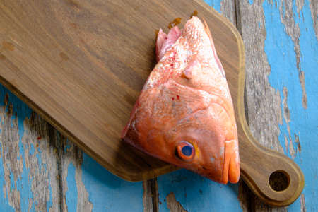 Fresh red snapper on wooden cutting board .
