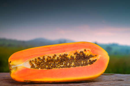Half cut ripe papaya with seed onon old wooden table with nature background. Natural medicine