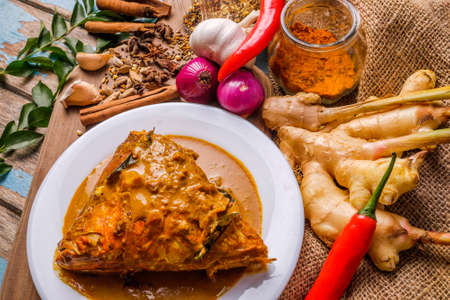 Delicious fish head curry served in a white plate over a wooden cutting board with some spices