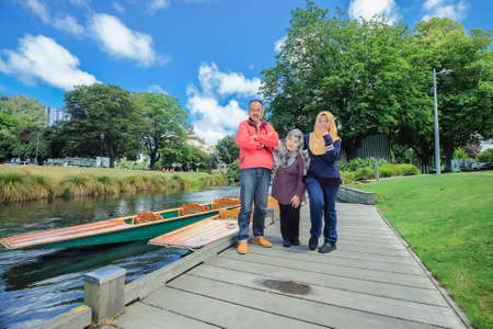 Christchurch, New Zealand – December 14th ,2017 :  Young girl wearing hijab  with her parents posing near the Punting boat shed on the Avon river Christchurch. New Zealand.