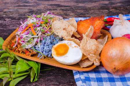 Fried chicken with rice and a combination of vegetables, duck eggs and ingredients in the plate