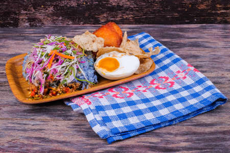 Nasi kerabu traditional in Malaysia food . Its blue color. Use coconut which has been fried and mixed with rice. a combination of vegetables, duck eggs and side dishes Stock Photo
