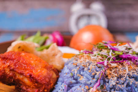 Nasi kerabu traditional in Malaysia food and alarm clock over old wood. Its blue color. Use coconut which has been fried and mixed with rice. a combination of vegetables, duck eggs and side dishes