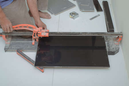 Worker Cutting Floor Tiles With Manual Cutter At Construction