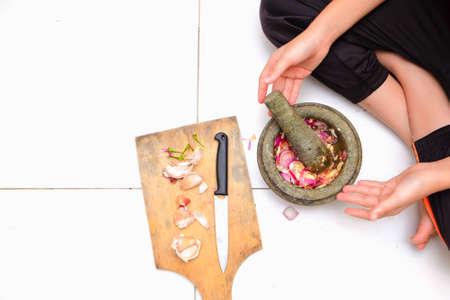 An Asian boy  is using the mortar and pestle or lesung batu in Malay with crushed chilies, onions and garlic for cooking rice fried 写真素材