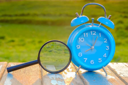 Alarm clock and magnifying glass standing on  wooen table against green background