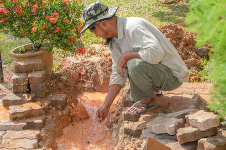 Muadzam Shah, Malaysia – February 8th, 2018  : Pipe contractor repairing leaking under the interlocking bricks walkway without any safety equipment like helmet or boots.