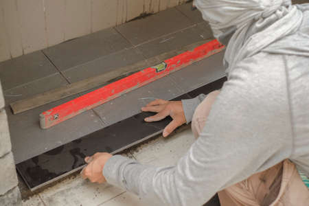 Construction worker tiler is installing floor tile at repair renovation work.Kitchen renovation  and improvement.