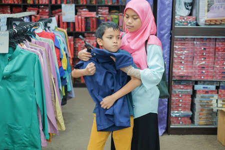 Segamat, Malaysia -  February 25th, 2018 : Young boy trying new Baju Melayu , malay traditional cloth for Eid Fitr   in the cloth store at Jakel , Segamat, Malaysia.