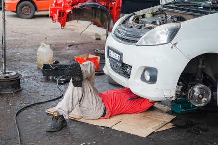 Muadzam Shah , Malaysia - December 28th, 2017 :  Mechanic in red shirt  lying down and working under car at auto service garage Editorial
