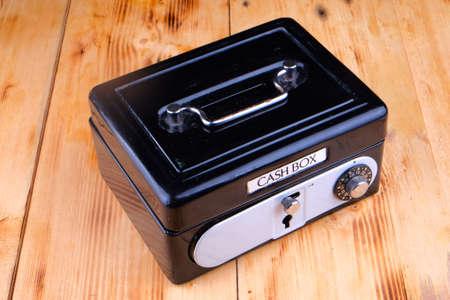 Cash box on the wooden table Фото со стока