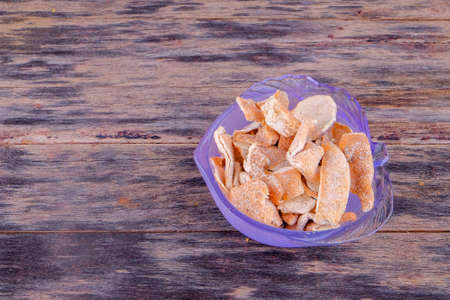 Sour orange peel in glass bowl over wooden table