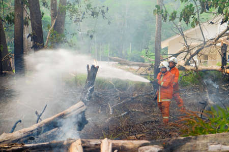 Muadzam Shah, Malaysia - May 7th, 2018: Two firemen wearing safety helmet spraying water to fire surround with smoke and dust in the bush fire.