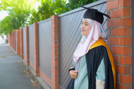 Beautiful female Muslim wearing a convocation robe and posed in happiness style after graduation ceremony.