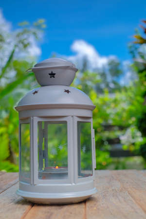 Lantern on an old wood with a blue sky as background. Ramadhan Concept.