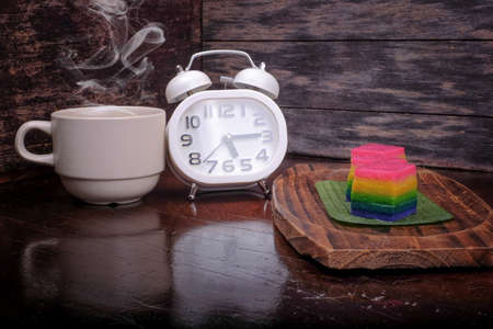 Traditional Malaysian food. Kuih Lapis , alarm clock and  a cup of coffee on wooden background. Coffee time concept Stock Photo