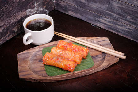 Traditional Malaysian food. Popia on wooden background. Coffee time concept