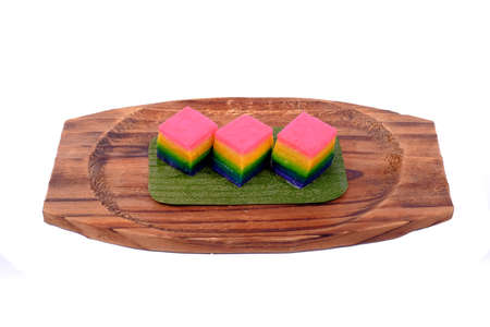 Traditional Malaysian food. Kuih Lapis over the wooden plate isolated on white background.