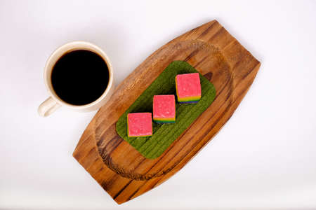 Traditional Malaysian food. Kuih Lapis and  a cup of coffee isolated on white background.