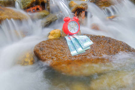 Time is money concept with money and alarm clock on river  . Imagens