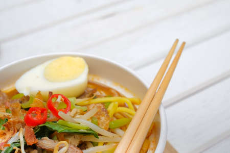 Mee Rebus in the bowl  with chopsticks on white table This dish is made of noodles ,vegetable,egg with a spicy . Archivio Fotografico