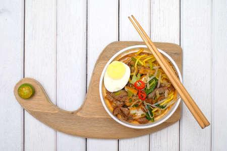 Mee Rebus nella ciotola con le bacchette sul tavolo bianco Questo piatto è fatto di tagliatelle, verdure, uova con un piccante. Archivio Fotografico