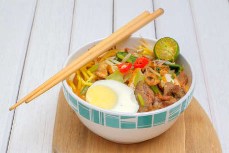 Mee Rebus nella ciotola con le bacchette sul tavolo bianco Questo piatto è fatto di tagliatelle, verdure, uova con un piccante.